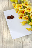 Chocolate hearts and gladioluses. Bouquet of beautiful yellow gladioluses, chocolate hearts and a blank sheet of paper for inscription on the wooden background Royalty Free Stock Image