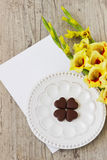 Chocolate hearts and gladioluses. Bouquet of yellow gladioluses, chocolate hearts and a blank sheet of paper for inscription on the wooden background. the idea Stock Image