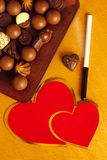 Chocolate hearts. Pen, red cardboard hearts and bunch of fine chocolate candies Royalty Free Stock Photos