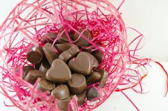 Chocolate hearts in a pink nest Stock Photos