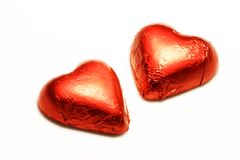 Chocolate Hearts in Red Foil. A pair of chocolate candy valentine hearts wrapped in shiny red foil are isolated on a white background Royalty Free Stock Photo