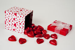Chocolate Hearts Spilling out of a Heart Gift Box. Heart Gift box tipped and spilling chocolate hearts Stock Images