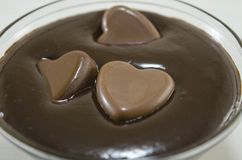 Chocolate hearts swimming in molten chocolate Stock Images