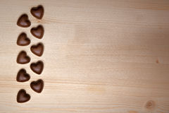 Chocolate hearts on valentine's day. Chocolate candy in a heart lined on wooden table Stock Image