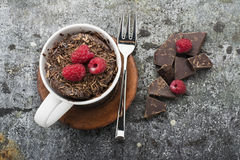 Chocolate homemade mug cake with chocolate chips, juicy fresh raspberries in a stylish striped gray mug with bits of. Bitter chocolate on a gray stone Stock Photos