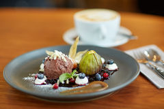 Chocolate ice cream dessert on plate at restaurant. Food, new nordic cuisine and sweets concept - chocolate ice cream dessert with blueberry kissel, honey baked Royalty Free Stock Photography