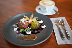 Chocolate ice cream dessert on plate at restaurant. Food, new nordic cuisine and sweets concept - chocolate ice cream dessert with blueberry kissel, honey baked Royalty Free Stock Photos