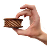 Chocolate Ice Cream Sandwich. Chocolate Ice Cream cookie Sandwich being held by a hand isolated on white background Royalty Free Stock Image