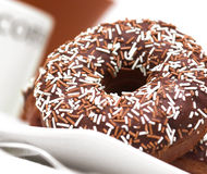 Chocolate Iced Ring Doughnuts. In a table setting Stock Images