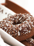 Chocolate Iced Ring Doughnuts. In a table setting Royalty Free Stock Photo