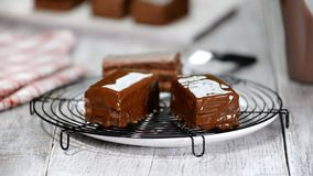 Chocolate icing on cake. Chocolate glaze pouring on homemade dessert. Close up of biscuit cake decoration. Topping