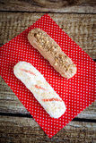 Chocolate and icing topping eclairs with chocolate and vanilla c. Ream on red fabric with dots Stock Image