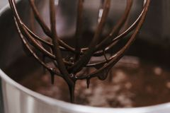 Chocolate immersed whisk close up view. recipe and bakery concept. Working places indoor royalty free stock photo