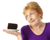 Chocolate Indulgence. Fit senior woman making food choices.  She is unable to resist the chocolate cake.  Isolated on white Stock Photo