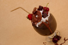 Chocolate indulgent extreme milkshake with brownie cake, strawberries, cherries, and a plastic straw with milk foam on Royalty Free Stock Images