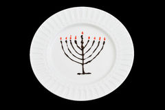 Chocolate and jam hanukkiah on a white plate and black background. Chanukkiah is a symbol of light and mircale happened on the Jewish hanukkah holiday stock photo