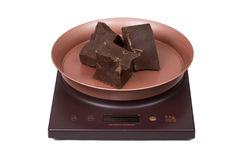 Chocolate on the kitchen electronic scales Royalty Free Stock Photos