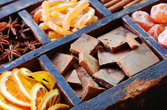 Chocolate, kumquats and spices in wooden display Stock Photos