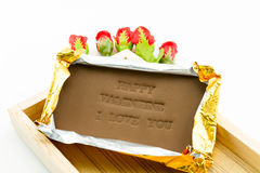 Chocolate labeled happy valentine i love you. On a wooden box. Roses adorned with a white background Stock Photo