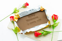 Chocolate labeled happy valentine i love you. On a wooden box. Roses adorned with a white background Royalty Free Stock Photos