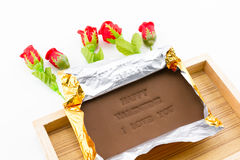 Chocolate labeled happy valentine i love you. On a wooden box. Roses adorned with a white background Stock Images
