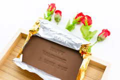 Chocolate labeled happy valentine i love you. On a wooden box. Roses adorned with a white background Stock Photography