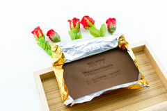 Chocolate labeled happy valentine i love you. On a wooden box. Roses adorned with a white background Royalty Free Stock Photo