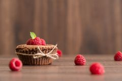 Chocolate lava cake with mint and fresh pieces of raspberries on the table. Chocolate lava cake with mint and fresh raspberries on the brown wooden table Royalty Free Stock Image