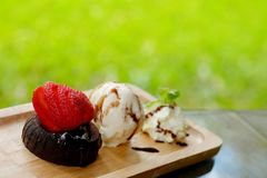 Chocolate Lava cake Served with Strawberry and Vanilla ice cream whipping cream set on wooden tray in summer time with day light. Stock Images