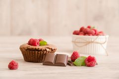 Chocolate lava cakes with fresh raspberries, mint and chocolate pieces. On wood board. Tasty and sweet pie Stock Image