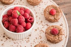 Chocolate lava cakes with fresh raspberries, mint and chocolate pieces. Chocolate lava cakes with fresh raspberries and mint on the plate. Tasty and sweet pie Stock Photo