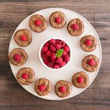 Chocolate lava cakes with fresh rspberries and mint leaf arranged in a circle on the porcelan plate. Delicious chocolate lava cakes with fresh raspberries and Stock Photography