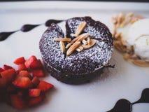 Chocolate lava. Chocolate fondant lava cake on white ceramic dish served with fresh strawberry and vanilla ice cream Royalty Free Stock Image