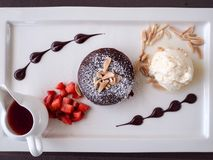 Chocolate lava. Chocolate fondant lava cake on white dish served with fresh strawberry and vanilla ice cream Stock Image