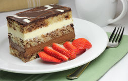 Chocolate Layer Cake. A piece of chocolate layer cake served with sliced strawberries and coffee Royalty Free Stock Image