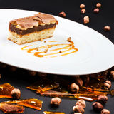 Chocolate Layer Cake with caramel, nuts and chocolate on white p Stock Photo