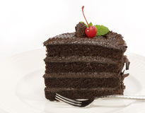 Chocolate Layer Cake - slice. A slice of frosted chocolate layer cake on white plate Stock Image