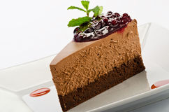 Chocolate layered mousse cake with dark cherries. On a plate Royalty Free Stock Images