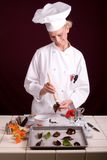 Chocolate Leaf Painting. Passive posed smiling uniformed female Pastry Chef painting a citrus leaf with melted dark chocolate Royalty Free Stock Photography
