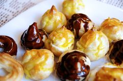 Chocolate and lemon-vanilla profiteroles. Chocolate and lemon-vanilla glazed profiteroles or choux buns on a white plate Stock Photo