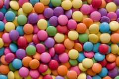 Chocolate lentil candies. Closeup of a large group of overlapping colorful chocolate lentil candies stock photos
