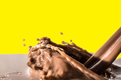 Chocolate liquid splash, pouring stream jet of chocolate, cocoa,. Isolated on yellow background stock photo