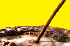 Chocolate liquid splash, pouring stream jet of chocolate, cocoa,. Isolated on yellow background royalty free stock photos