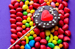 Chocolate lollipop on arranged candies Stock Images