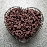 Chocolate Love. Chocolate morsels in a heart shaped dish on a kitchen counter Royalty Free Stock Images