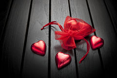 Valentine Love Chocolate Heart Background. Chocolate love heart chocolates covered with red foil outside and inside a mesh bag on a black table background Stock Photography