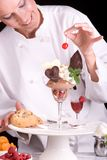Chocolate lovers dessert. Close up shot of a Dessert Chef topping an elegant chocolate ice cream sundae with a red cherry Stock Photography