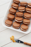 Chocolate macarons. Delicate and elegant chocolate macaroons with white cream on white plates Stock Photography