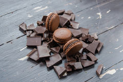 Chocolate macarons over pieces of chocolate on wooden background. Close up. Stock Image