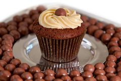 Chocolate Malt Cupcake. On steel plate surrounded by malt balls Stock Photo